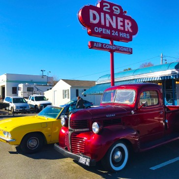 A colorful collection of vintage cars out front.